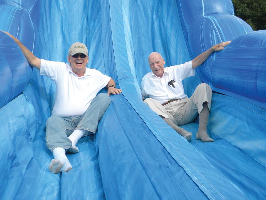 SLIPPING AND SLIDING: Doug Brush is remembered as a generous and inspiring person at West Bay Christian Academy, but he is also remembered for his involvement at events. Above, Brush (right) and former board member Dr. Don Zeyl get in on the fun, sliding down an inflatable slide at the school's 30th Anniversary Event in 2011.
