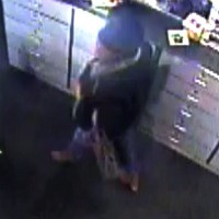 This image from surveillance footage shows a woman taking a Microsoft Xbox One game system from GameStop.