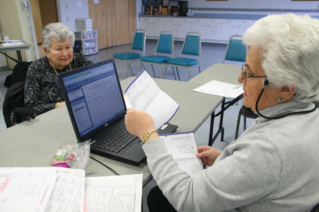IT TAKES A VOLUNTEER: Sylvia Dulgarian, who before retiring worked in an office where she did administrative work and accounting, assists Lorraine Weissman in the preparation of her tax return at the Pilgrim Senior Center. Dulgarian says she likes math and numbers.