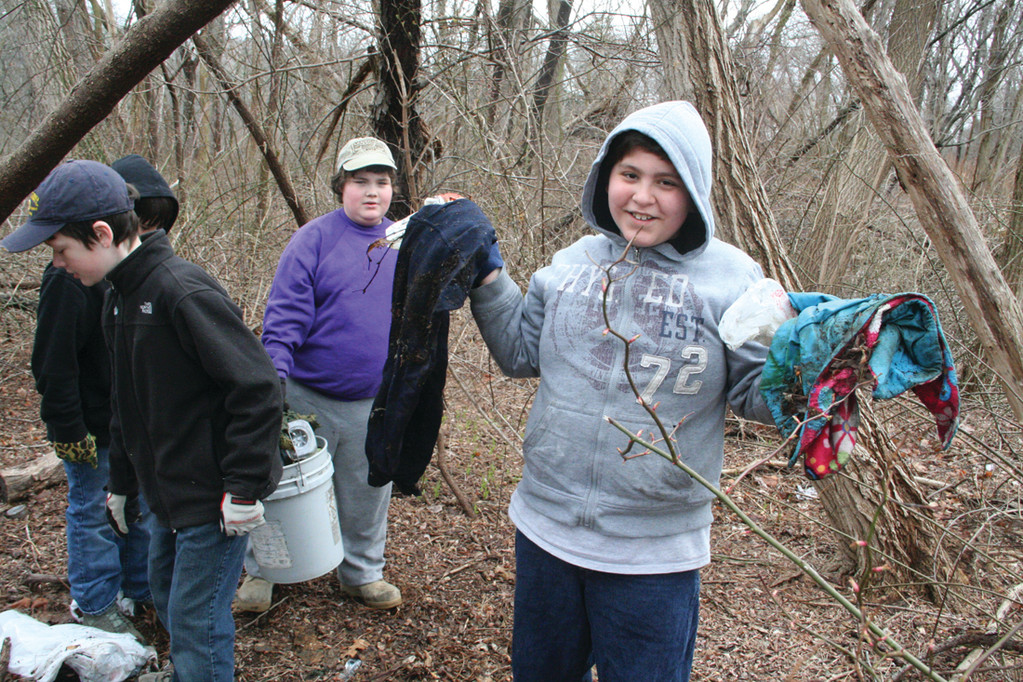 YUCK: Nate Moore of Troop 7 Buttonwoods holds up rotted clothing pulled from the underbrush