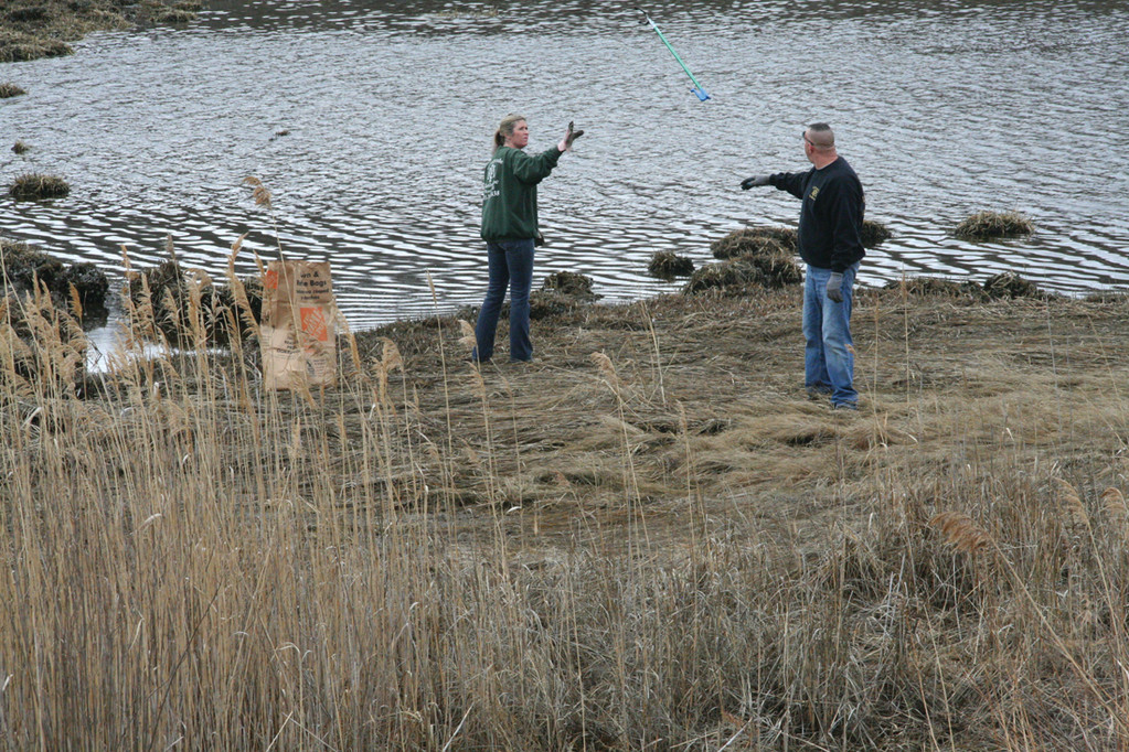 GOOD CATCH: Amy Patenaude reaches out to catch a tool from her husband, Rich, as they cleaned up the Warwick Cove salt marsh Saturday.