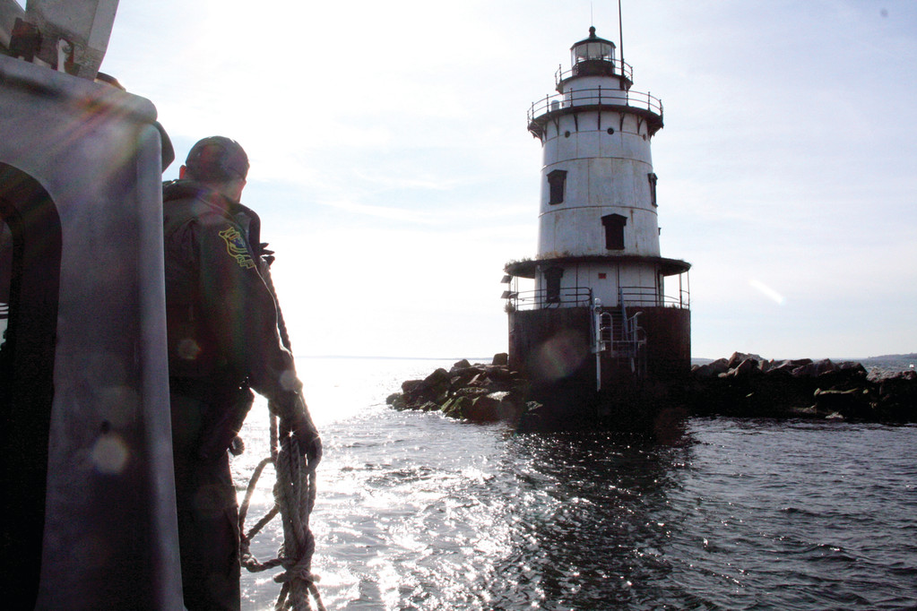 READY FOR VISIT: A crew member aboard a DEM vessel prepares to land a group of city officials at Conimicut Light in November.