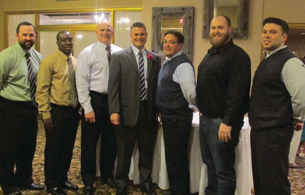 TOP HONORS: Bishop Hendricken High head football coach Keith Croft (fourth from left) is joined by his assistant coaches after he received the Providence Gridiron Club's overall Coach of the Year last Wednesday night in North Kingstown. The coaches are, from left: Jason Hogan, Brandford Sowah, Joe Bucci, Mike Green, Mike Sackett and Frank Pantaleo.