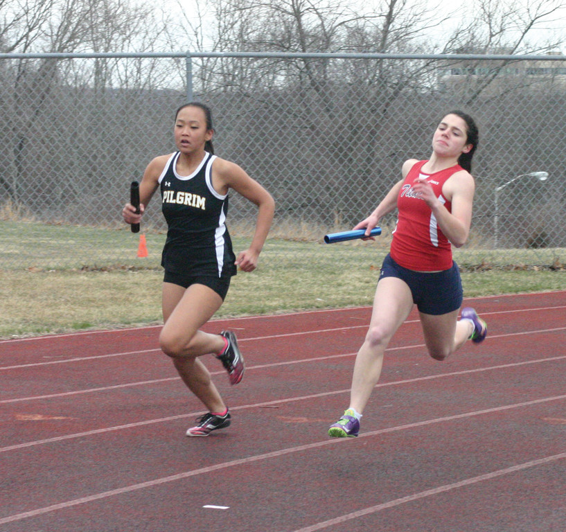 NECK AND NECK: Pilgrim's Claudia DeMelo and Toll Gate's AnneMarie Martella round a curve in the 4x100 relay.