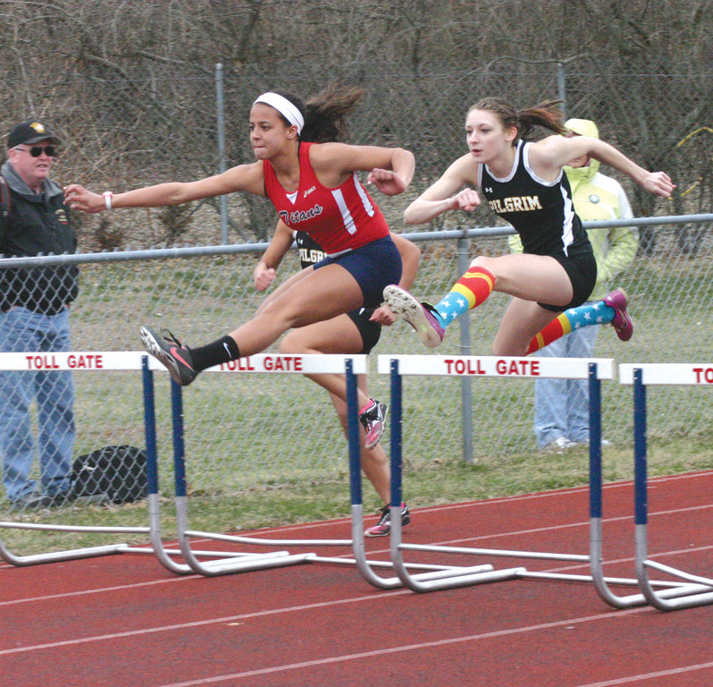 CLEARING IT: Pilgrim's Melanie Brunelle and Toll Gate's Erika Pena compete in the hurdles during Monday's city track meet. The Pilgrim boys and girls both beat Toll Gate and Vets.