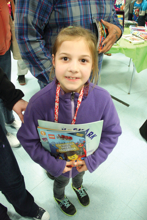 JUST WHAT SHE WANTED: First grader Kyleigh Minn clutches books she selected at the sale set up in the school gym and run by the PTO.