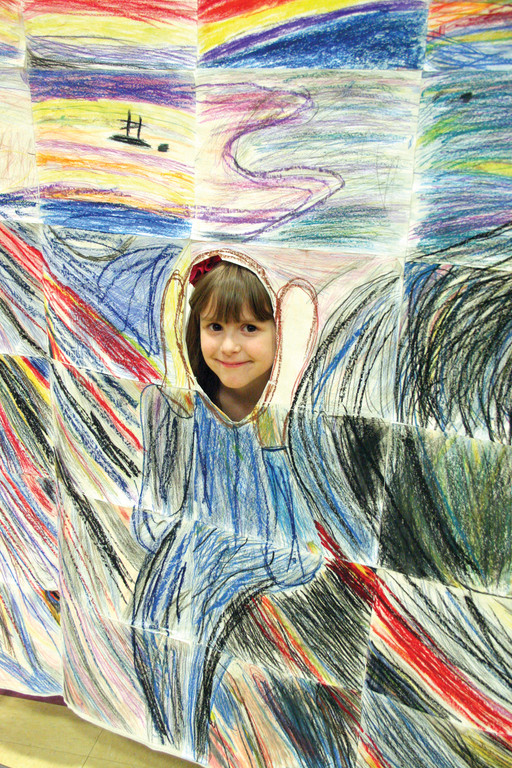 "A SMILE INSTEAD OF A SCREAM: First grader Isabella Varrecchione flashes a smile from the cutout of a facsimile of Norwegian painter Edvard Munch's ""The Scream."""