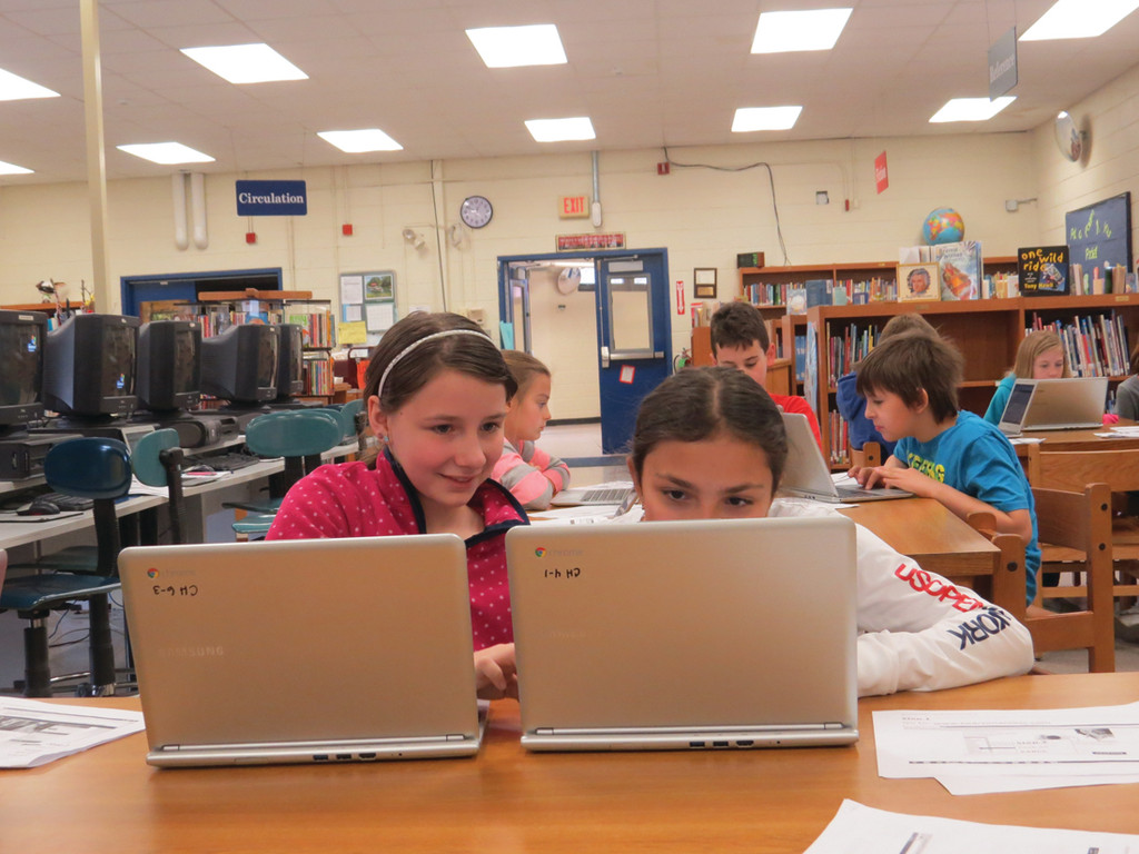 TEACHING ONE ANOTHER: After taking part in the practice test, the students had the opportunity to use the Chromebooks to visit any website they liked. Fourth-grader Macey Higgins and a friend seemed to enjoy their opportunity to use the new technology following the formal training workshop.