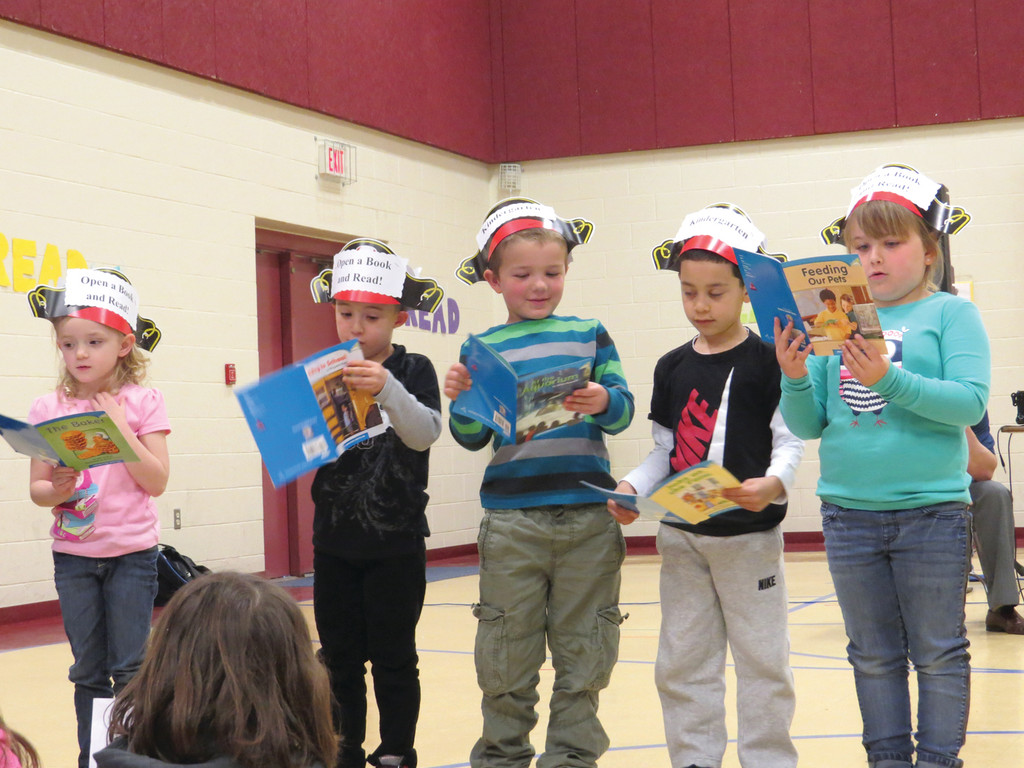 OPEN A BOOK: Kindergarteners Haylen Hoel, David Ferante, Logan Legauly, Carlos Gonzalves and Cassidy Thompson joined with their classmates to recite a poem about books and reading during Randall Holden School's Reading Week and NECAP Spring 2014 Celebration Assembly.