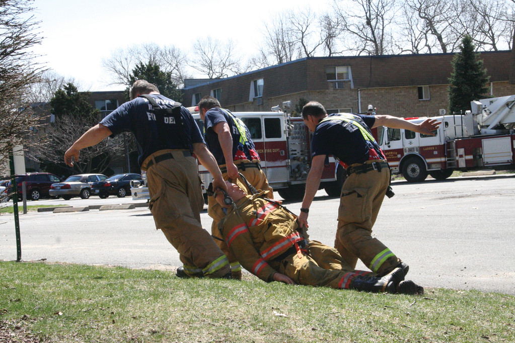 DEAD WEIGHT: Firefighters drag the dummy, weighing about 250 pounds, after completing the exercise.