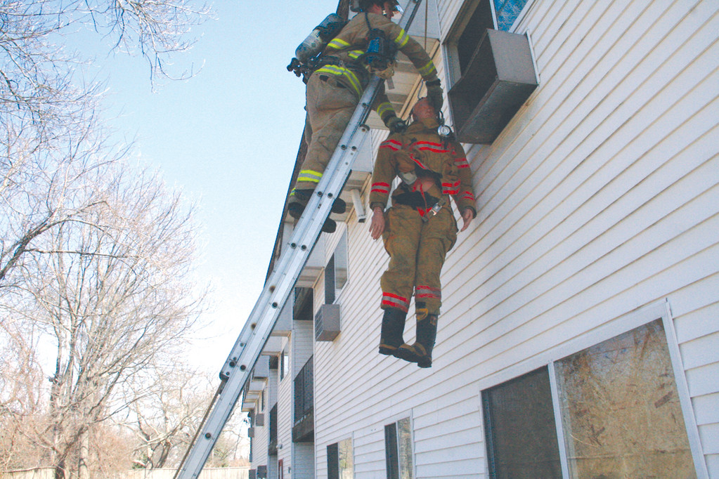 GETTING HIM OUT: Using a rope, harness and clip system, a single firefighter is able to lower another to the ground safely.