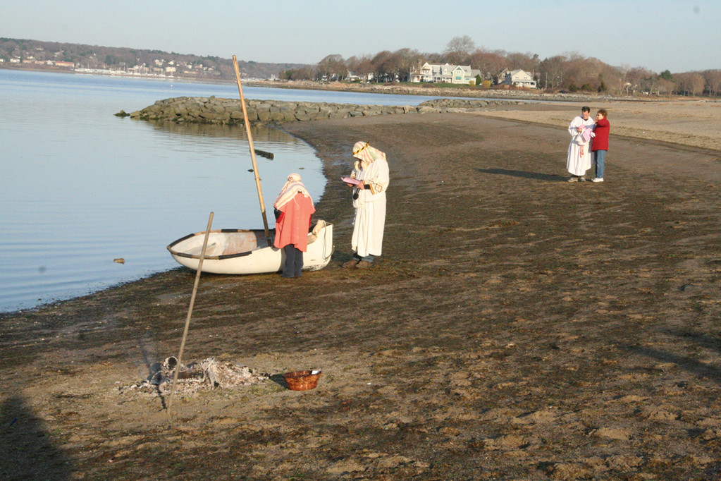 PREPARING FOR REENACTMENT: Jesus played by Bill Moulton, at far right, goes over his script as those who played disciples ready nets at the fishing boat.