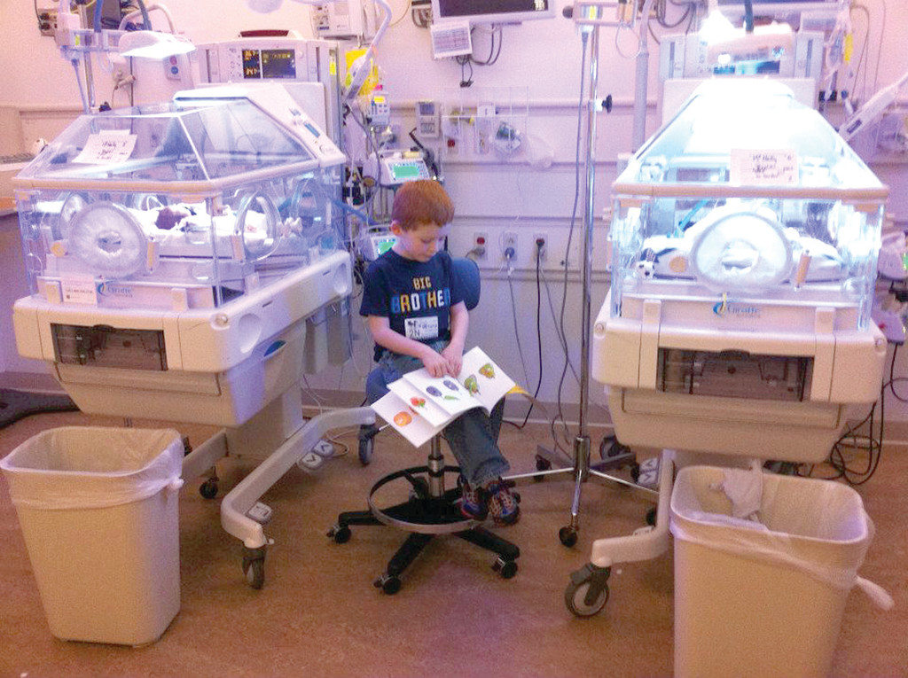 LOVE IS THE BEST MEDICINE: Ben McNally reads to his sister and brother while they are in the NICU.