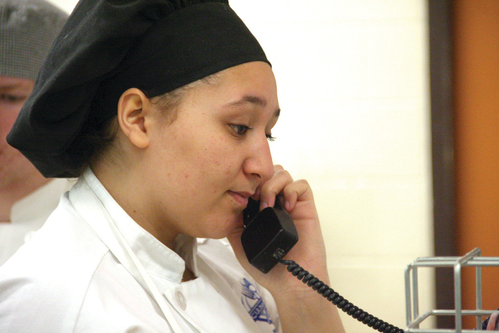 GETTING OUT THE WORD: Triyana Bates, a Pilgrim student, takes a call about center restaurant hours, making a plug, as well, for Friday's May breakfast.