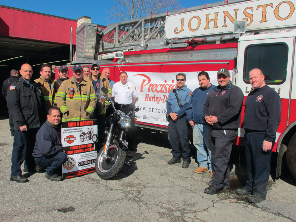 FOR A GOOD CAUSE: Members of the Johnston Firefighters Local 1950 IAFF, AFL-CIO gather around the 2014 Harley Davidson Fat Boy Motorcycle they�re raffling off.