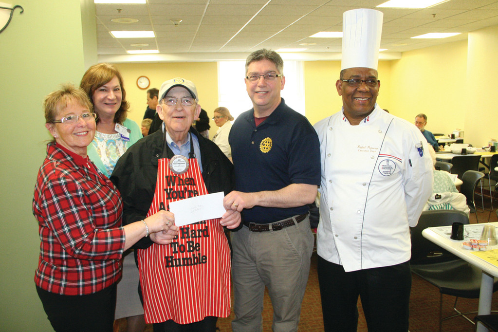 KEEP IT COMING: Carolyn Yuettner and Rebecca Lukowicz of the hospital pose with Joseph DesRoches of the Warwick Rotary Club, club president, and hospital chef Rafael Reguere with a check presentation to KEEP [Kent Employee Emergency Program].