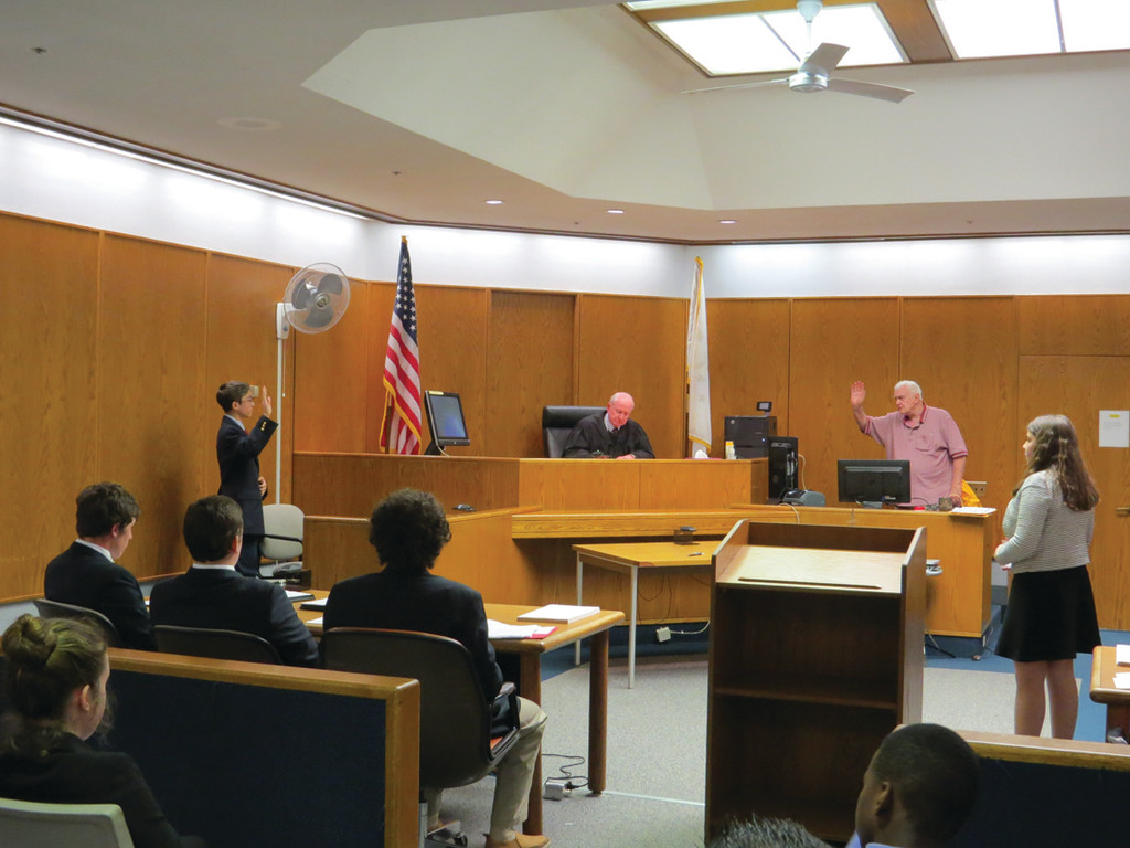 QUIET IN THE COURTROOM: Student Alex Sinapi, who portrayed the plaintiff Alex Day, is sworn in as classmate Maddy Cuddy (far right) prepared to question him during Tuesday's State Mock Trial Championship. The trial took place in Courtroom 4B at Providence's Garrahy Judicial Complex before Judge Edward P. Sowa.