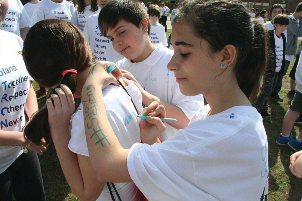 SIGNING UP: Seventh grader Valentina Ranero signs the anti-bullying t-shirt of her classmate Brianna Lin Fraser