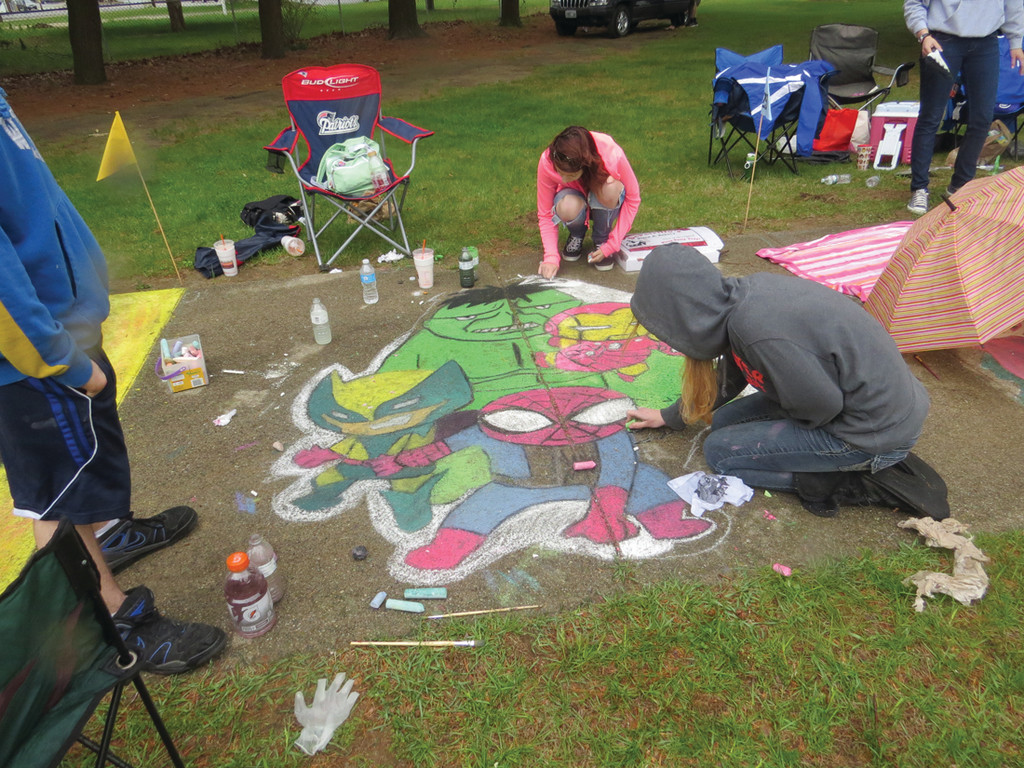 MAKING THE BEST OF IT: Brianna Thomas and Ciara Mazza continue working on their Marvel-inspired design, using the rain to their advantage. To give their work a paint-like finish, the students often apply water to the chalk to smooth out the color. Many students used a paintbrush directly on the wet cement to give the same effect.