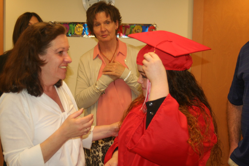 GETTING READY FOR HER BIG MOMENT: Cranston West's Liz Romeiro helps Tiffany with the final details of her graduation attire while West's Holly Meyer looks on.