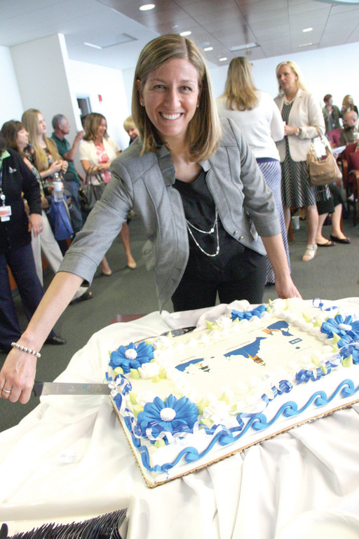 SLICING INTO A NEW MARKET: Nancy Shane, vice president of training and employee development at Cape Air, cuts the cake welcoming new service to Block Island in ceremonies Thursday. The airline has a staff of 1,000.