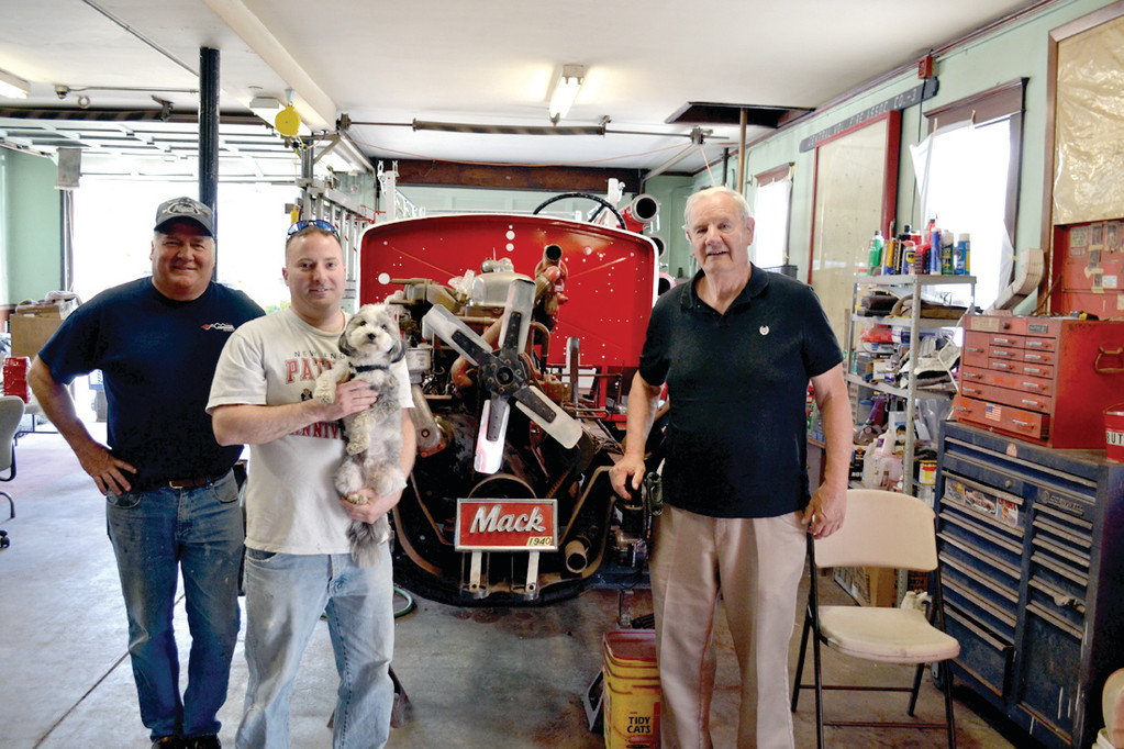 DOWN TO NUTS AND BOLTS: Retired Chief Kenneth Smith (left), his son Nathan holding Company Mascot Milton, and Retired Battalion Chief Raymond Bartlett stand in front of the partially dismantled 1940 Mack Truck, which has undergone an extensive restoration campaign for the last four years.