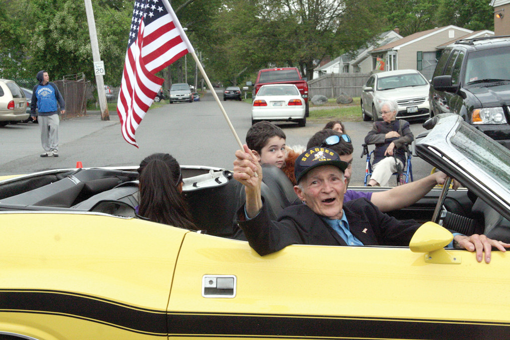 FLAG COMES FIRST: World War II veteran Ray Forcier waves to those who turned out to celebrate Memorial Day at yesterday's Veterans Council parade. While a few drops greeted marchers as they stepped off from the Hendricken High School parking lot, by the time they reached Vets High and the review stand, skies had brightened.