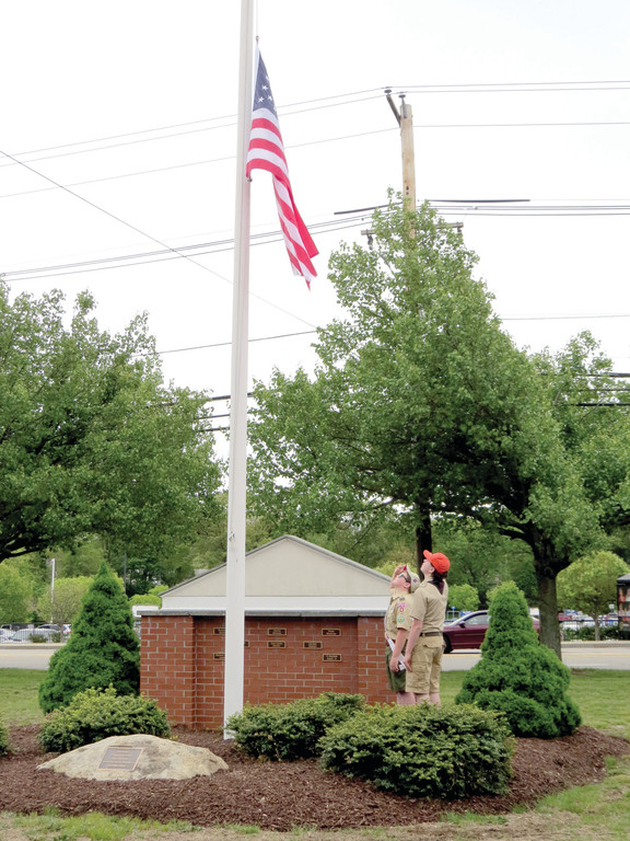 SOLEMN SALUTE: Eighth graders Andrew Fredericks of Boy Scout Troop 4 Gaspee Plateau and Luke Ferguson of Boy Scout Troop 1 Gaspee Plateau salute the flag, put at half-mast for the ceremony, during the singing of the national anthem.