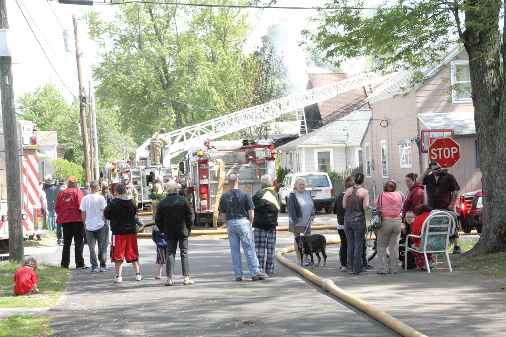 SCENE ON HURON STREET: Neighbors and family of Eileen Ryan gather in the street as firefighters battle the fire that extensively damaged her home Thursday morning.