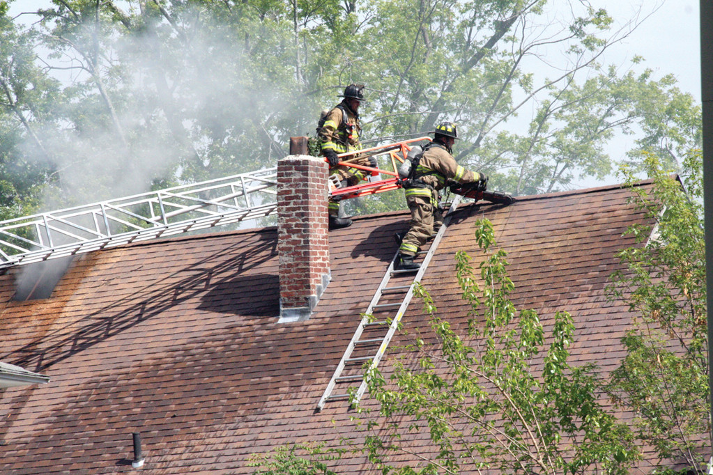 VENTING THE FIRE: Using a saw to cut through the roof, firefighters work to reach smoldering timbers.