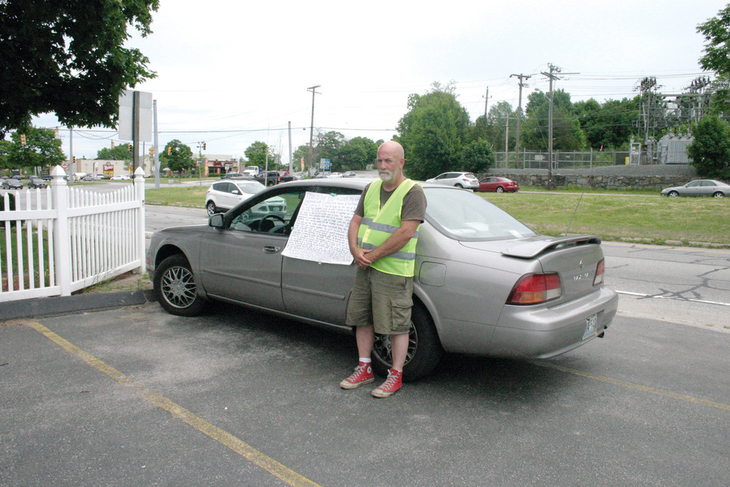 LOOKING FOR DONATIONS: Bill Roche stands next to a poster with a detailed explanation of his story attached to his car as he waits for donations from drivers.