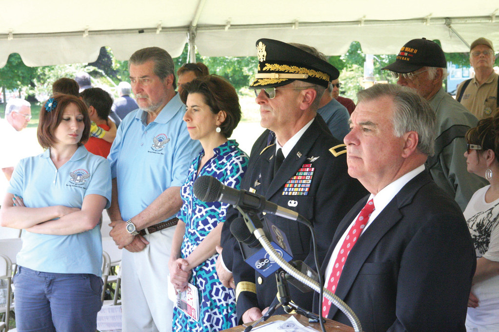 AT CEREMONY: Participants in Saturday�s ceremony look out toward the wall during the event. They are from left: Anthony DeQuattro, president of Operation Stand Down Rhode Island, General Treasurer Gina Raimondo, Brigadier General Charles E. Petrarca Jr. and RI Supreme Court Justice Francis X. Flaherty.