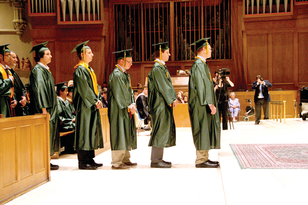 ONE MORE STEP: Hendricken seniors clad in green and gold gowns stand in line anxiously waiting for their diplomas. Hendricken graduated 197 students in the class of 2014 last Friday night.