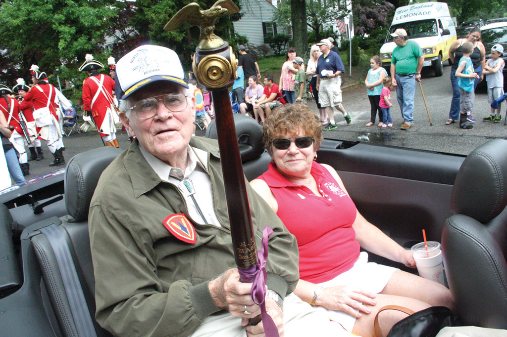 PARADE MACE BEARER: A Marine veteran of Iwo Jima, Tad Comstock of Exeter, N.H., holds the Rhode Island Mace as he drives with his daughter, Janet Russell, in the 49th annual Gaspee Day parade. The mace supposedly contains wood from the Gaspee that was burned by colonists 242 years ago. (Warwick Beacon photos by John Howell)