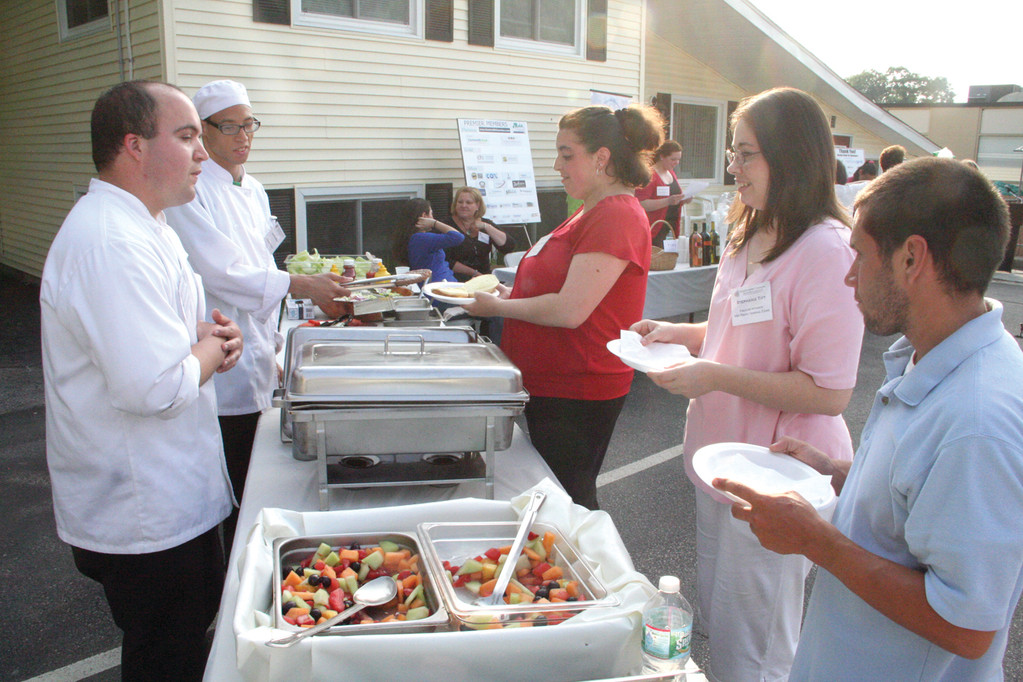 SERVING UP JOBS: Patrick Marino and Justin Reid work the chow line at the Business After Hours hosted by the Trudeau Center Employment Concepts Tuesday evening. They are serving Christine Sweeney, Stephanie Tift and Micah Sukenik, all Trudeau clients involved in the Employment Concepts program.
