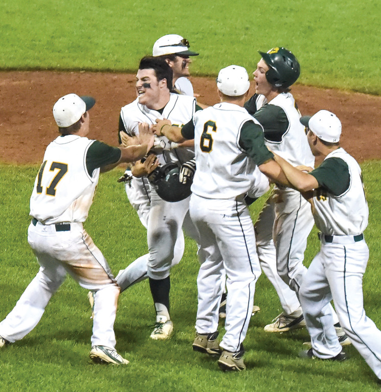 THE BIG ONE: John Toppa is mobbed by teammates after his walk-off hit in game one.