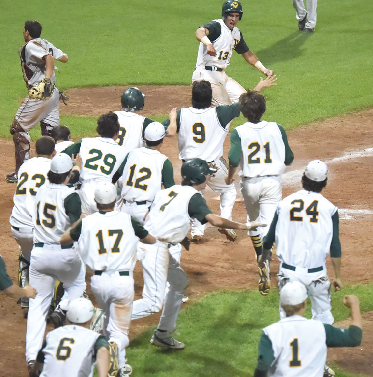 MOB SCENE: Hendricken players race to home plate after Gian Martellini scored the game-winning run in game one of the state championship series.