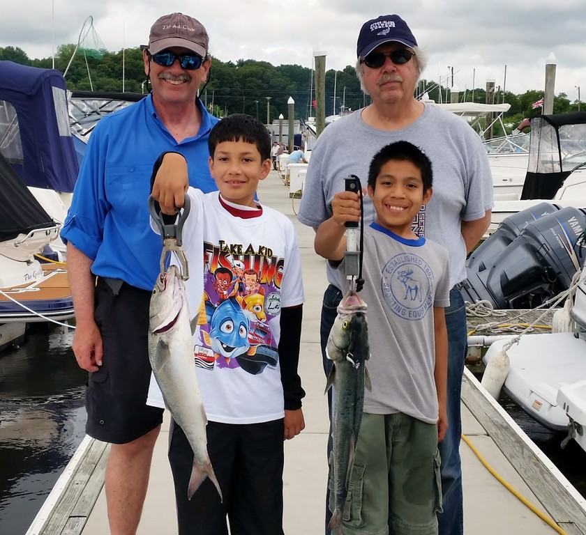 Capt. Dave Monti (left) and Pete Sousa (both of Warwick) took Lester and Alex from Boy Scout troops in Providence fishing.  A total of over 180 children fished during RISAA's Take-a-Kid Day Saturday.