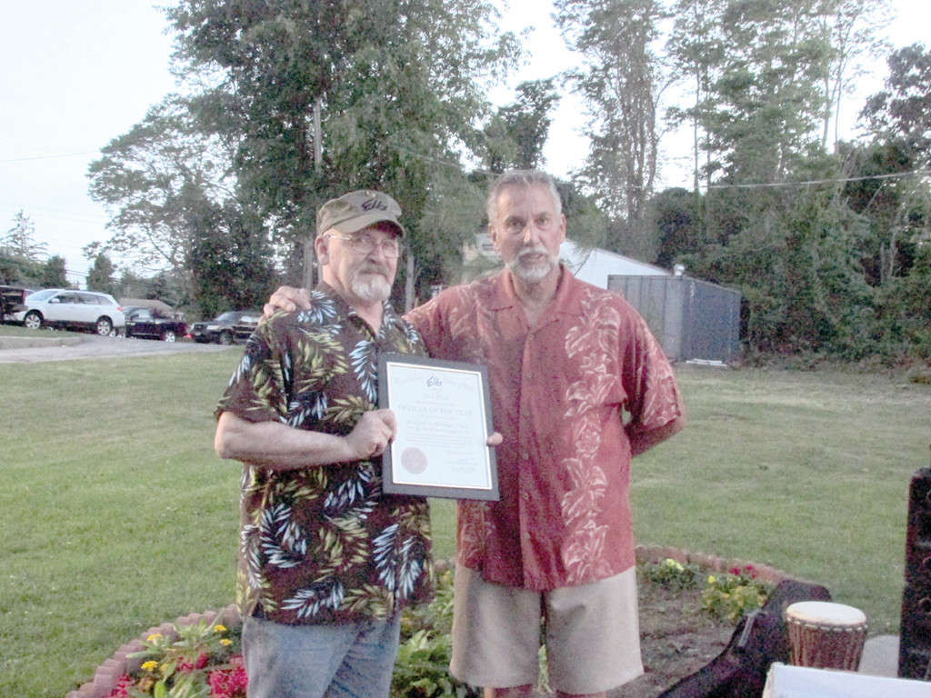 SUPER SERVICE: Albert �Cookie� Delory (left) shows off his Engineer of the Year Award presented by Tri-City Elks Lodge Exalter Ruler Mark Eaton during last Friday�s special summer kick-off party in Warwick. Delory was a key figure in Lodge 14�s ambitious remake, both inside and outside.