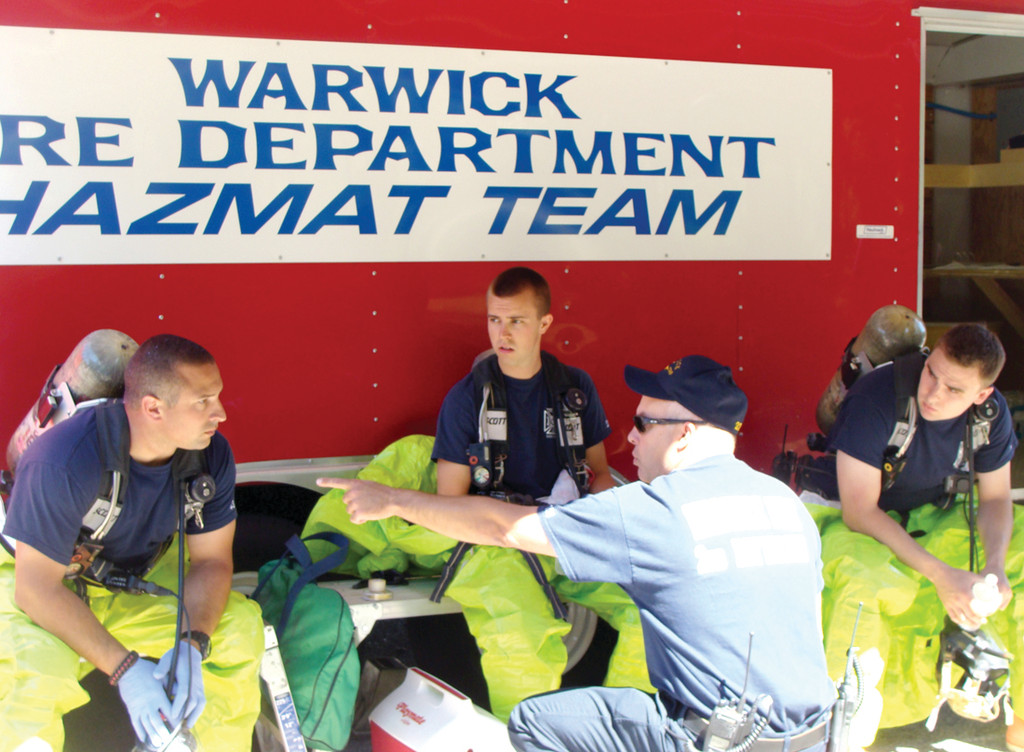 TRAINING DAY: Twenty Hazmat team technicians from the Warwick Fire Department participated in an eight-hour training day on Monday in full gear. Chris Sullivan, Matt Wood and Corey White (pictured from left to right), members of the entry team, waited in the shade listening to instructions in full gear.