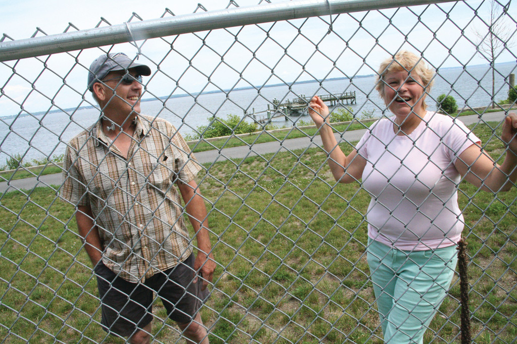 WHAT'S HAPPENING? Walter Belonos and Sue Bergeron interrupted their Rocky Point shoreline walk Thursday to inquire what a crew was doing inside the fence. Behind them are the remnants of the park dock. Gov. Chafee had included $2.5 million in a bond issue to appear on the November ballot for a new dock, but those funds are now tagged to go to Roger Williams Zoo.