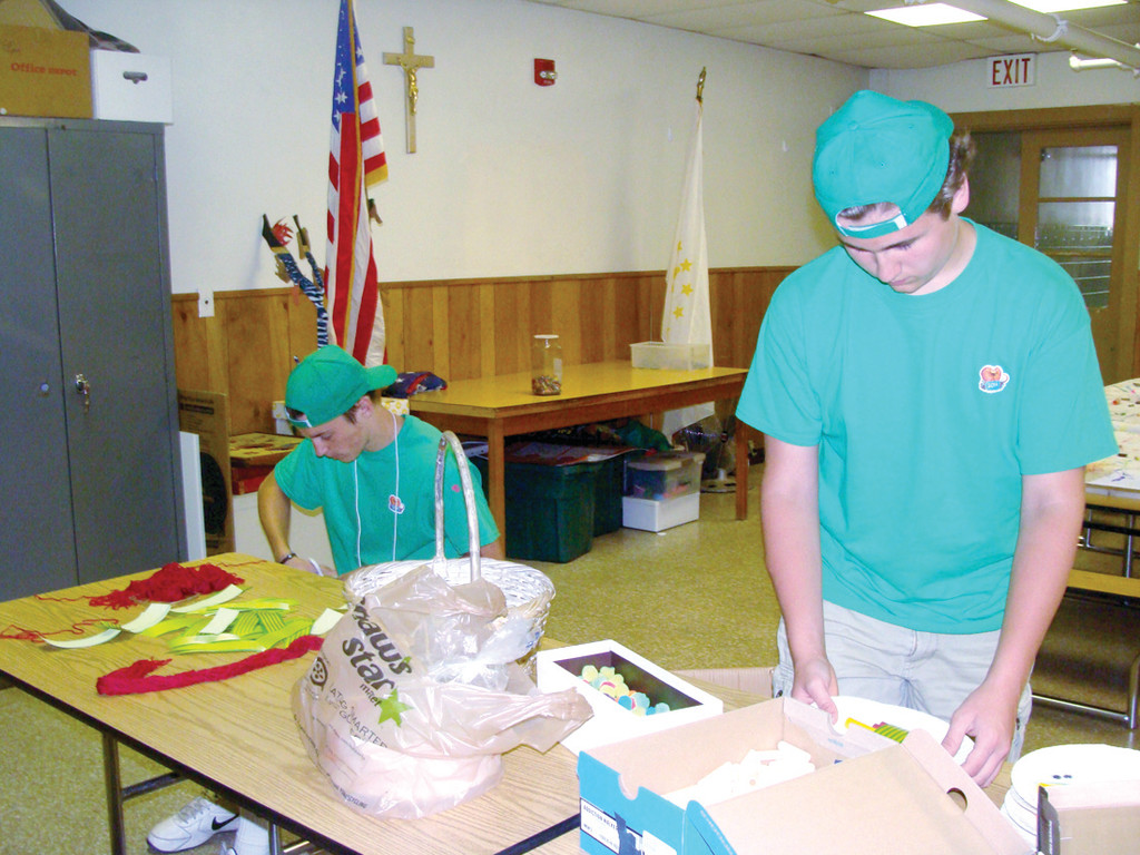 "VOLUNTEERS: Patrick Reilly and Steven Pezzullo, two senior counselors, help prepare supplies for the art station where students made mini marionette with phosphorescent paint and paper plates. Reilly had attended the camp himself before volunteering to be a counselor. He said, ""We just help out to make sure things go smoothly that the kids are having fun learning a lesson about God."" Both boys will receive community service hours for their help."