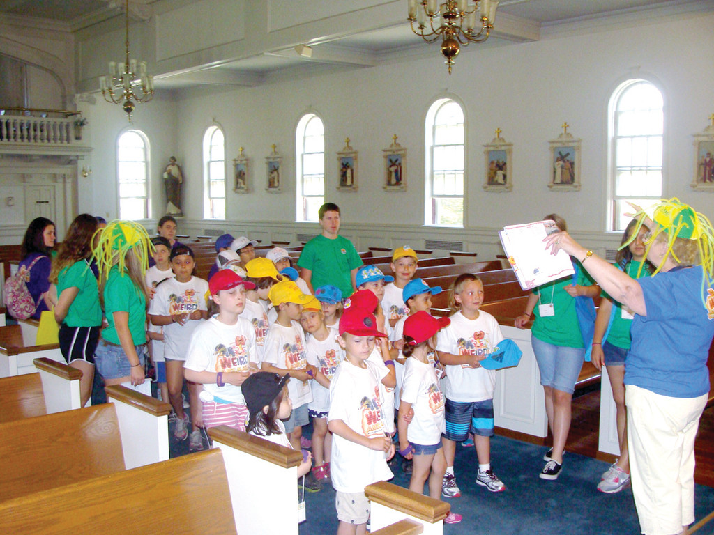 BIBLE TIME: One of the stations at the St. Peter's Vacation Bible Camp involves campers learning different stories from the Bible as they are acted out. Elaine Morisseau is pictured preparing the campers for the lesson. She and her helpers each day discuss a Bible verse and add characters and visuals to help the message be more accessible to the young campers.