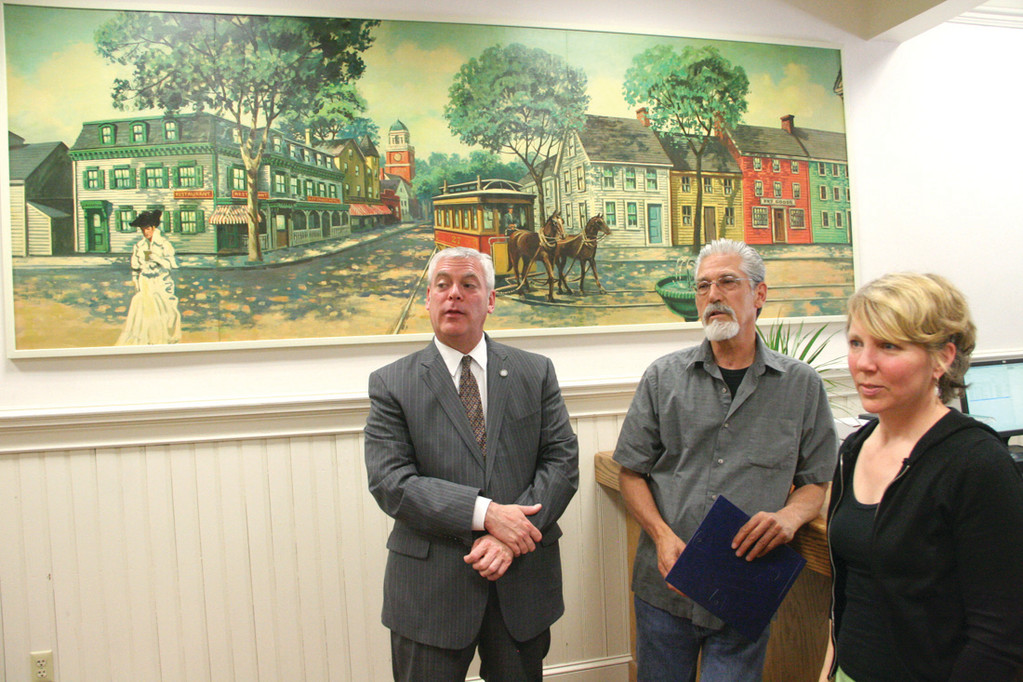 IN NEW HOME: Art restoration specialists Roy Collins and Amie Hannon Boesch talk with Mayor Scott Avedisian following the hanging of a mural they restored Tuesday in the City Hall office of City Clerk.