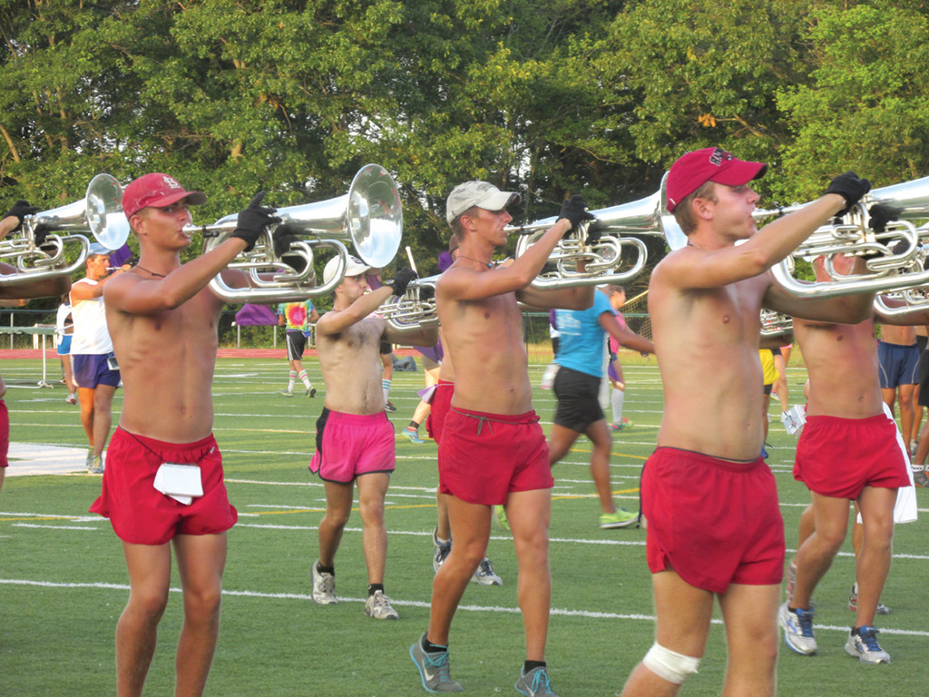 PREPARING FOR THE BRISTOL PARADE: Shorts, hats and headbands were the uniform of the night Tuesday in Warwick where the World Champion Carolina Crown practiced in preparation for two competitions and Friday's Bristol Fourth of July Parade. Above are members of the Baritone horn section.