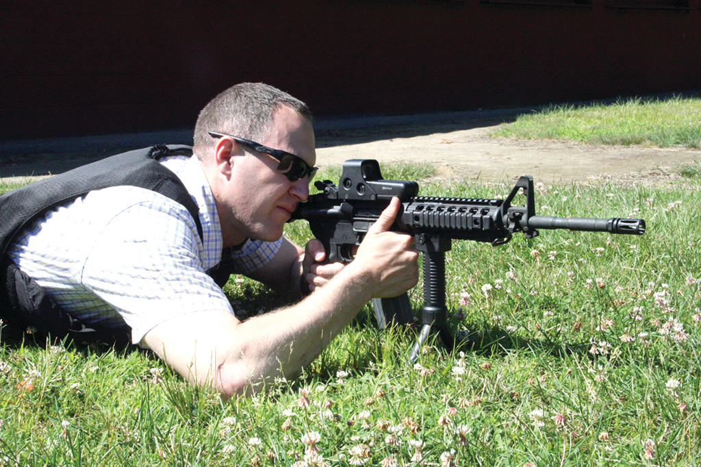 MAKING ADJUSTMENTS: Detective Brent Groeneveld zeros in his rifle�s scope to improve its accuracy at different distances from the target.