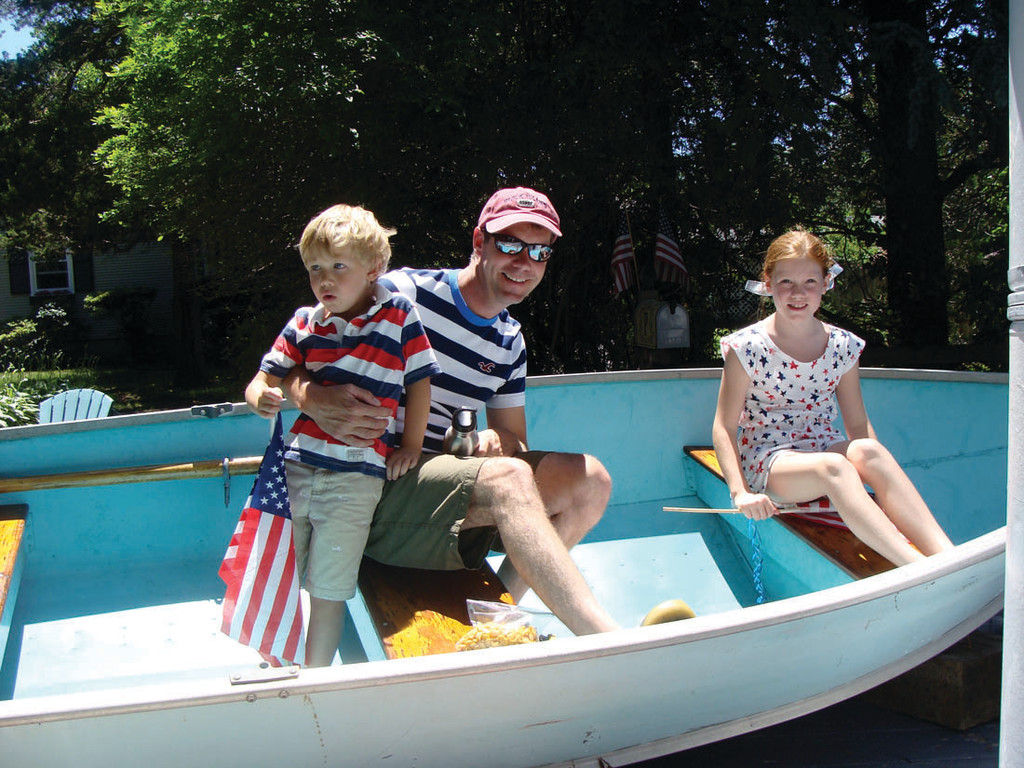 SAIL AWAY: Mark McHugh, with his children Alexa and Theo, rode in a sailboat float that had a lighthouse behind it. He is the president of the Warwick Neck Improvement Association.