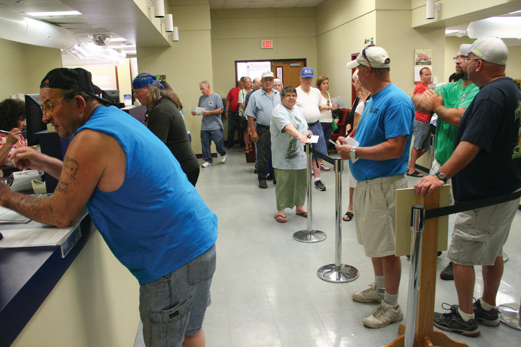 HOT STUFF: Taxpayers line up in the collector's office to make their first quarterly payment that is due July 15. With the air conditioning having failed, fans have been installed.