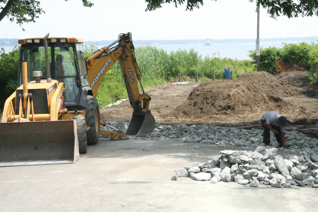END OF THE ROAD: About 90 feet of pavement has been removed from Mill Cove Road where it ends at Narragansett Bay. In its place crews are installing a stormwater drainage system aimed at reducing erosion as well as plantings designed to protect the area from storms.
