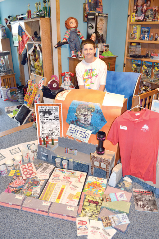 A RIDE THROUGH TIME: Fifteen-year-old Sean McCarthy sits in a lifelike recreation of a Rocky Point House of Horrors car, which he designed and built himself. Surrounding the car are just some of the many Rocky Point items he's collected during the past several years.